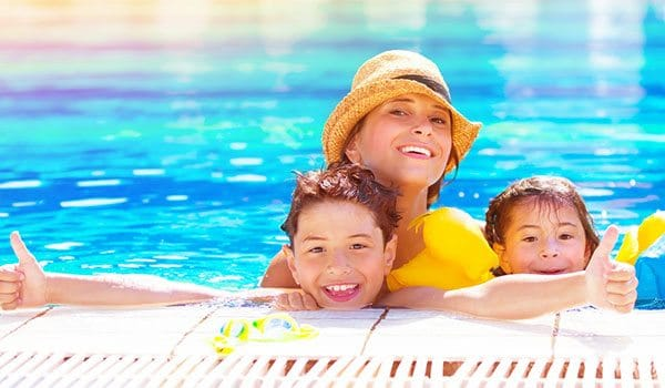mum and kids happy in a holiday village swimming pool