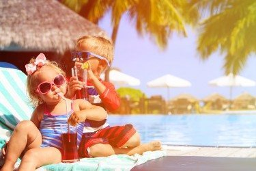 Kids sitting on a towel by the pool and drinking cordial