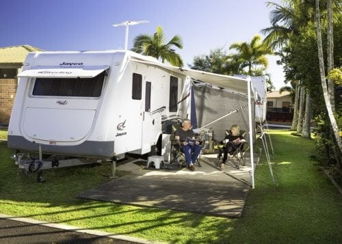 A Couple Enjoying Their Holiday In Front Of Their Caravan At Brisbane Holiday Village