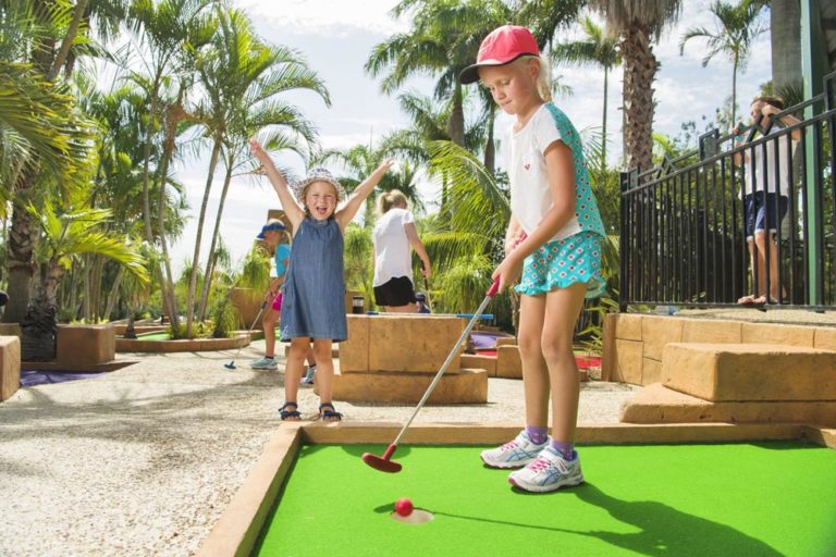 Two young girls playing mini-golf at Brisbane Holiday Village
