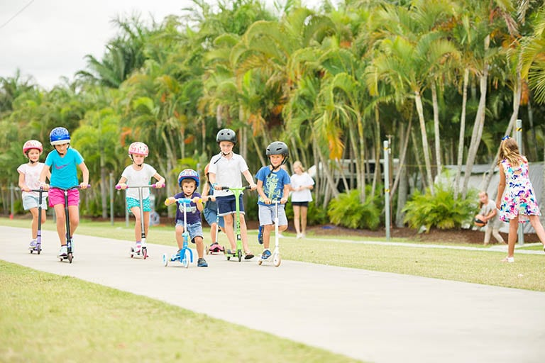 Kids playing and riding scooters and bikes on the bike path at Brisbane Holiday Village