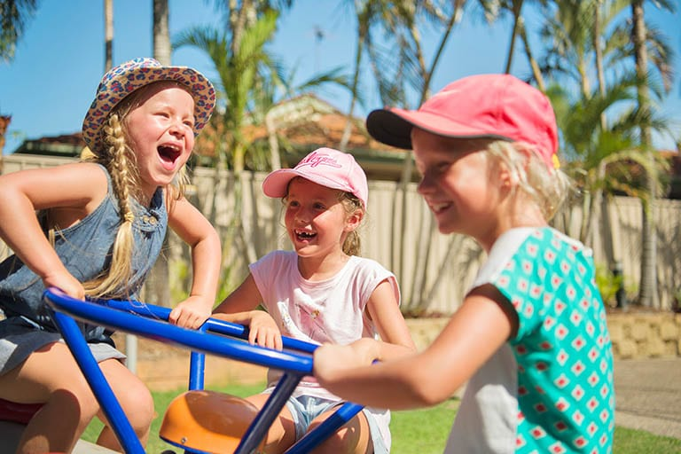 Three young girls playing on the balance playground equipment at Brisbane Holiday Village