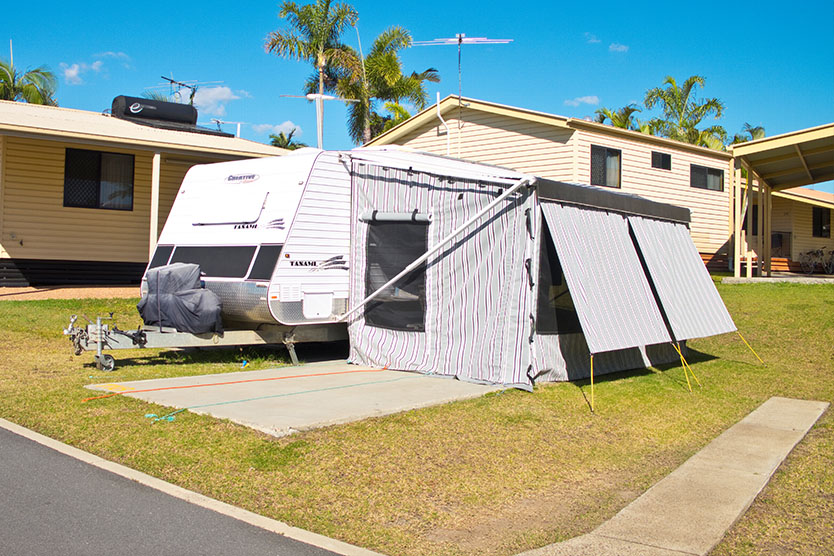 Side view of a caravan camp setup on a 7m to 9m caravan site at Brisbane Holiday Village
