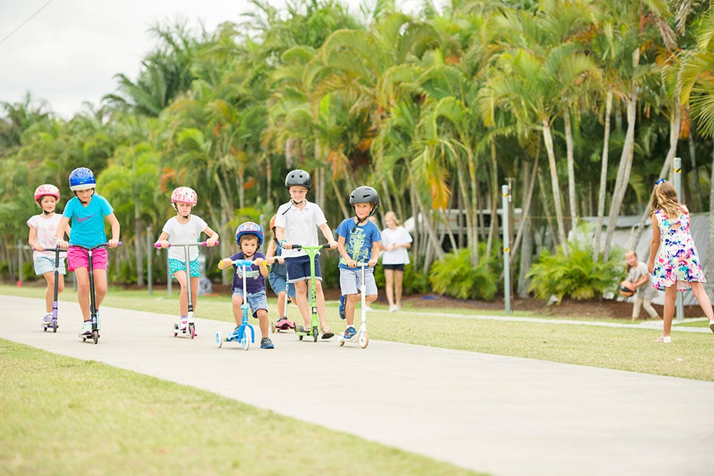 Large group of children riding scooters and bikes on the 350m Bike Track at Brisbane Holiday Village