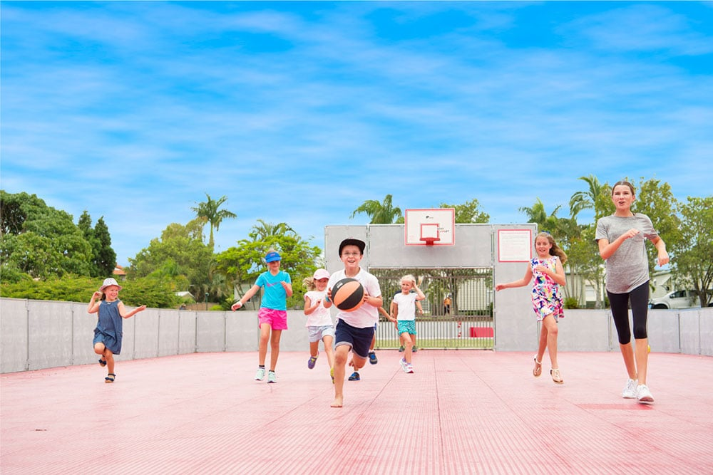 Group of children playing basketball on the multi-purpose sport field at Brisbane Holiday Village