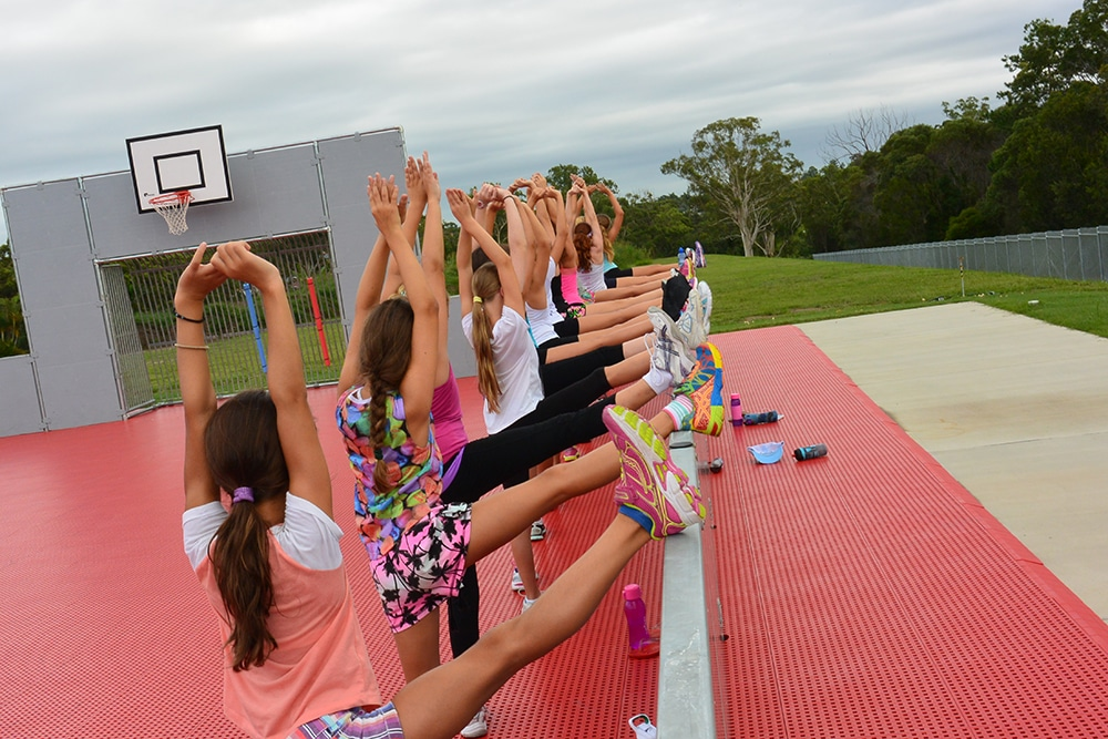 Women's Sports team stretching and exercising on the Multipurpose sports field at Brisbane Holiday Village