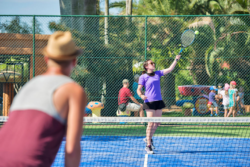 People playing tennis on the tennis court at Brisbane Holiday Village