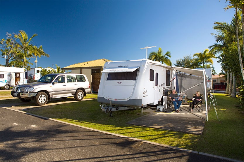 Family relaxing around their caravan camp on an ensuite site at Brisbane Holiday Village