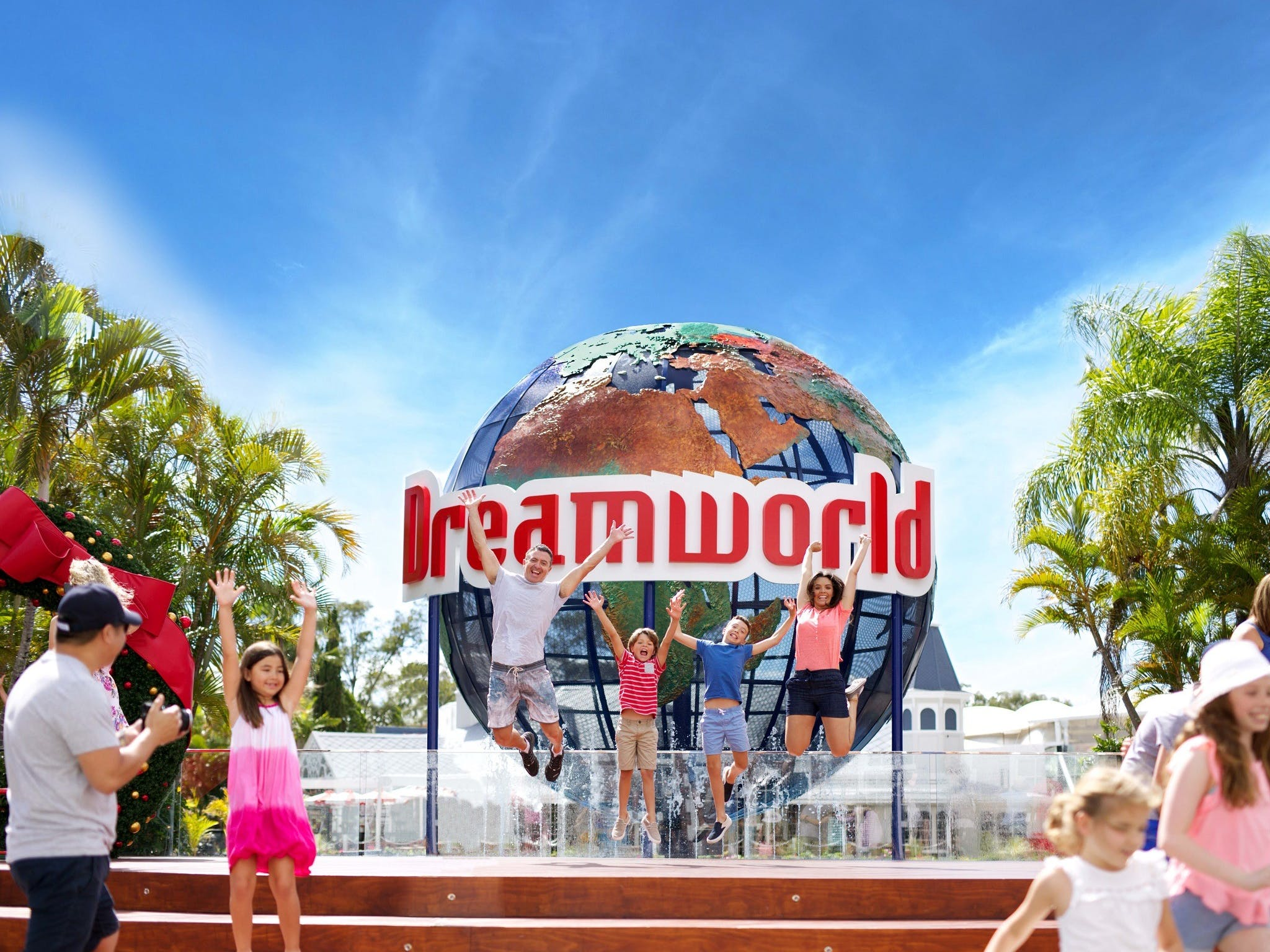 Family jumping for joy in front of Dreamworld theme park sign