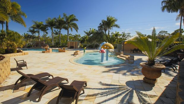 Lagoon area with pool lounges and kiddie pool with fountains at Brisbane Holiday Village